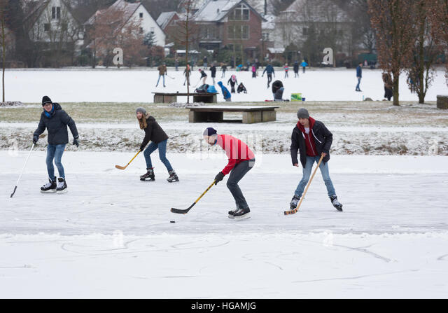 Local people enjoy a game of ice hockey on a frozen flooded meadow. - Stock Image