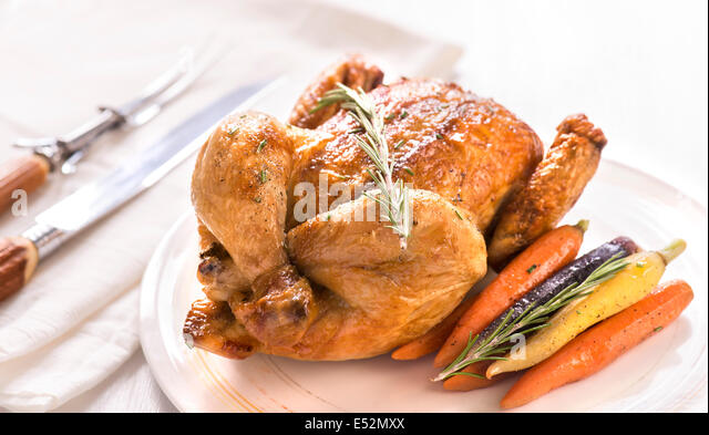 Whole roasted chicken on a plate with rosemary and rainbow carrots. - Stock Image