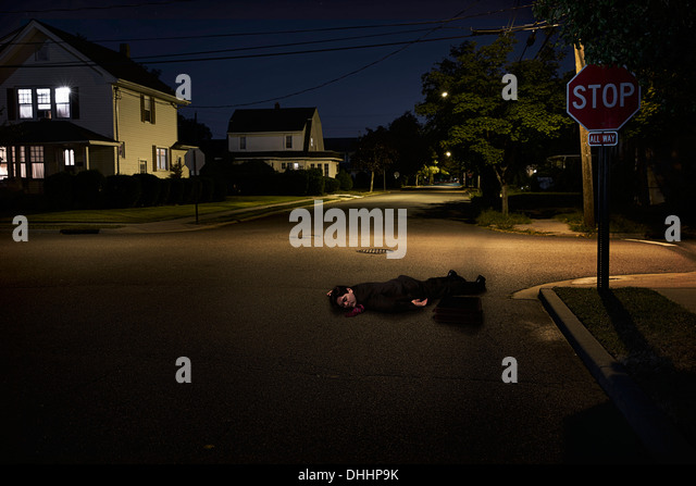 Businessman lying on suburban street unconscious at night - Stock Image