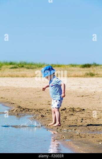 Small boy on beach throwing sand into sea, Marennes, Charente-Maritime, France - Stock Image