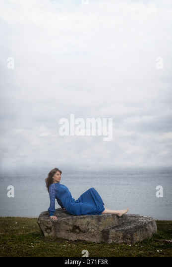 a girl in a blue dress is lying on a stone - Stock Image