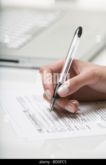 Woman filling out a tax form - Stock Image