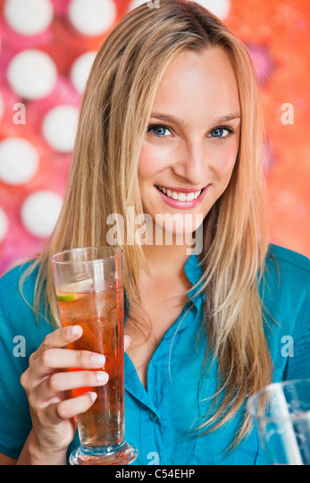 Portrait of a beautiful woman having ice tea in a bar and smiling - Stock Image