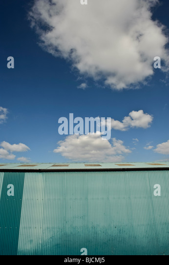 Blue painted corrugated iron shed, with white puffy clouds and blue sky UK - Stock Image