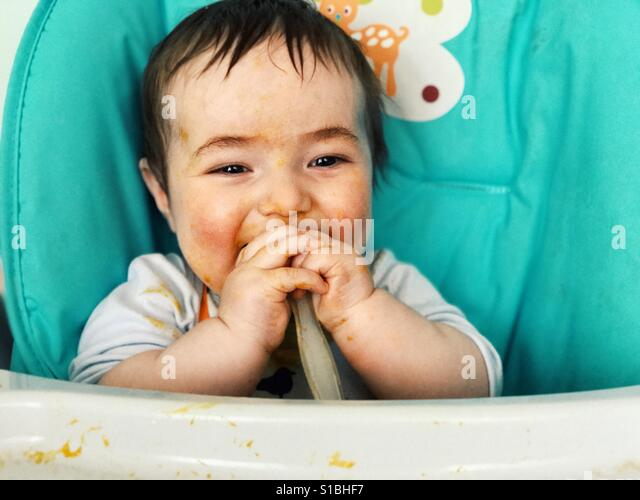 7 months old baby eating by himself - Stock Image