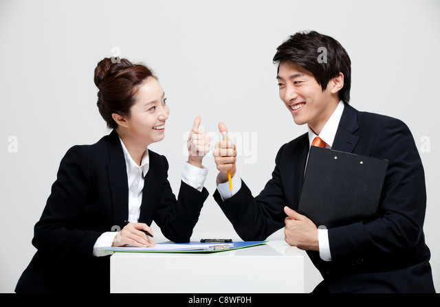 Asian Businessman And Businesswoman Showing Thumb Up Sign At Desk Facing Each Other - Stock Image