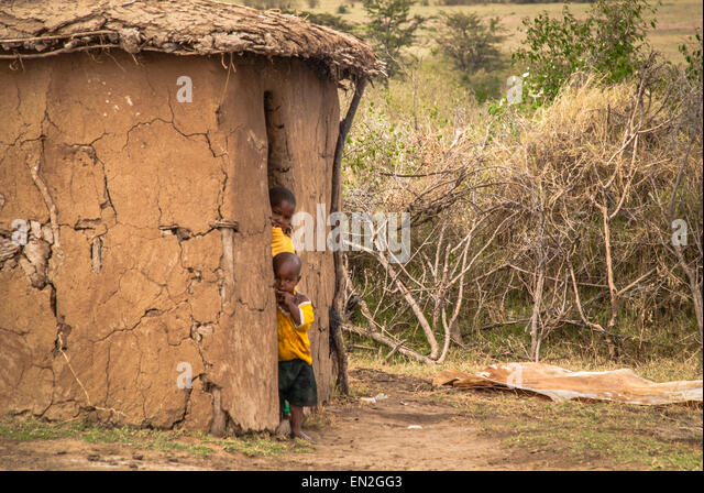 Two small Masai children peek out from a mud hut in a Masai Village. The huts form a kraal and is fenced by acacia - Stock Image