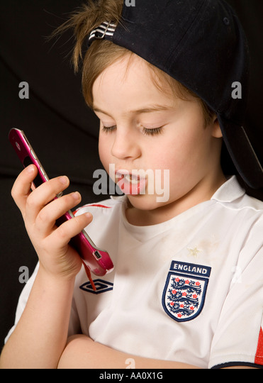 Face of a young boy wearing a reversed baseball cap speaking into a cell phone - Stock Image