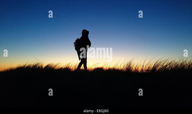 Silhouette of man walking in rural landscape at sunset, Denmark - Stock Image