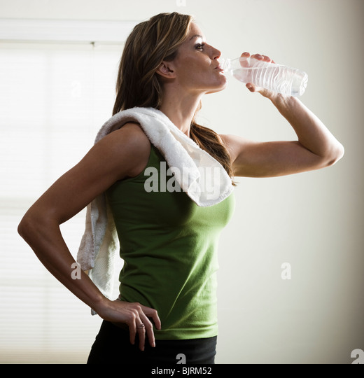 USA, Utah, Orem, young woman drinking water after exercising - Stock Image