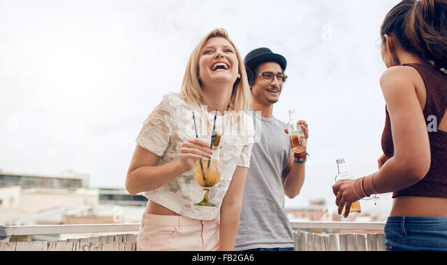 Portrait of cheerful young woman enjoying party with her friends. Young people having fun at rooftop party. They - Stock Image
