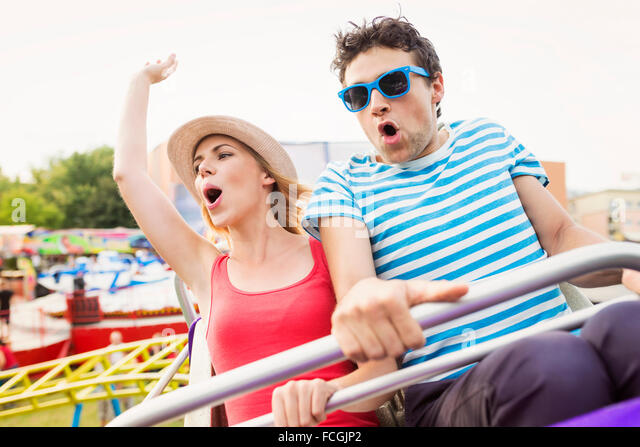 Happy couple at fun fair riding roller coaster - Stock Image