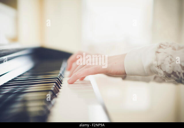 Close up of Caucasian girl playing piano - Stock Image