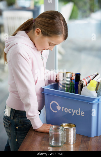 Girl (10-12) putting empty vessels into recycling container, side view - Stock Image
