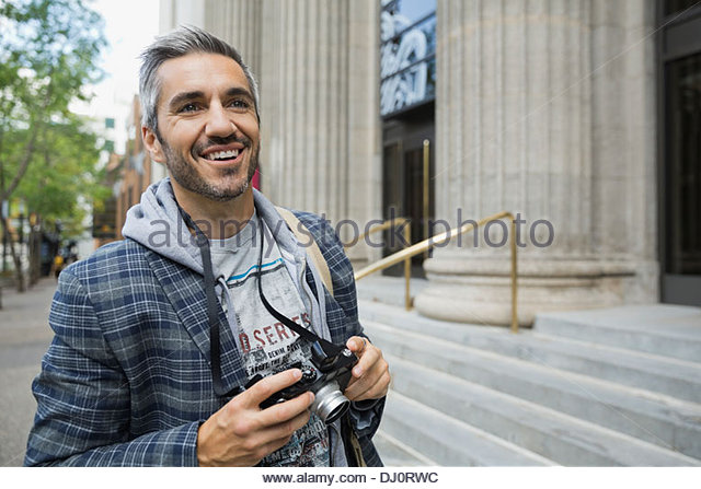 Man standing outdoors with camera - Stock Image
