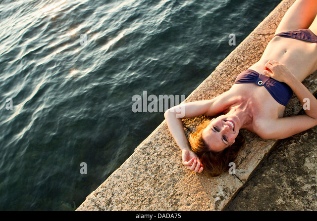 Woman lying on wall by the sea - Stock Image