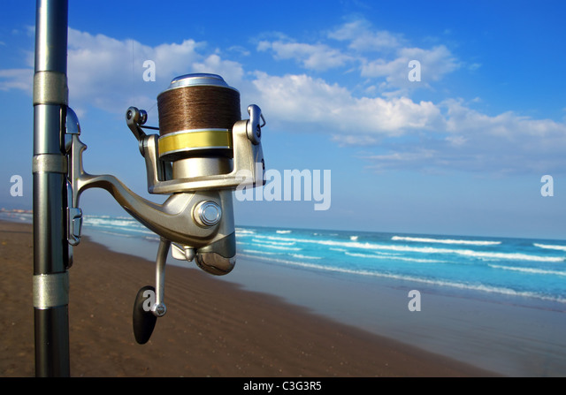 Beach surfcasting spinning fishing reel and rod in tropical sea - Stock Image
