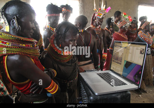 Loiyangaleni, Kenya. 19th May 2012. Turkana women of the Loiyangalani Stars group look at images and video taken - Stock Image