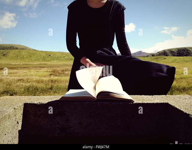 Midsection Of Woman By Retaining Wall With Book - Stock Image