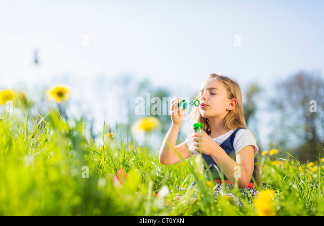 Girl blowing bubbles in field - Stock Image