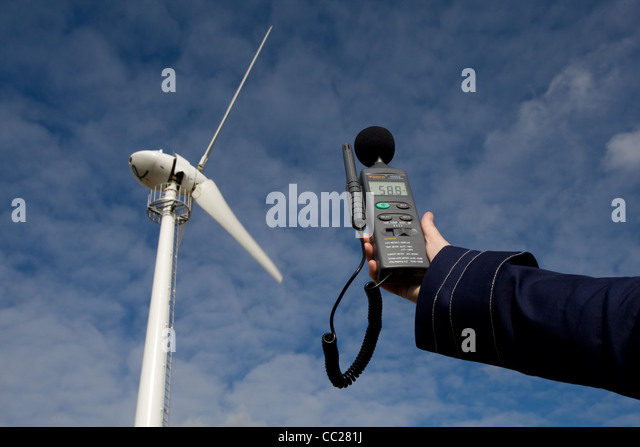 A sound level meter is held up to a wind turbine to measure the noise emitted in decibels. - Stock Image