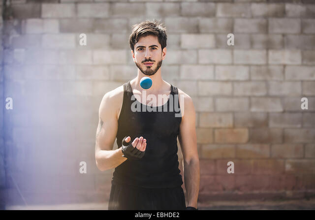 Portrait of young male handball player throwing ball - Stock Image