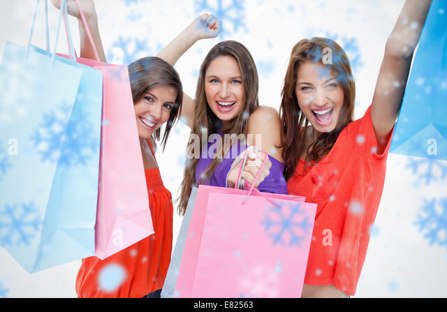 Young women elevating their purchase bags - Stock Image