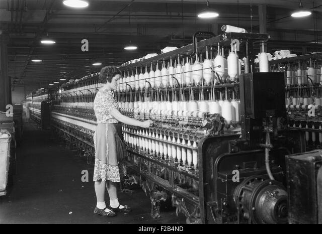 Woman standing at long row of bobbins, at a textile factory. Millville, N.J. 1936. Photo by Lewis Hine. - (BSLOC - Stock Image