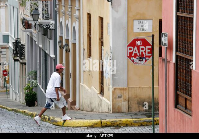 Puerto Rico Old San Juan Calle del Sol architecture steep hill Hispanic male adoquine cobblestone stop sign - Stock Image