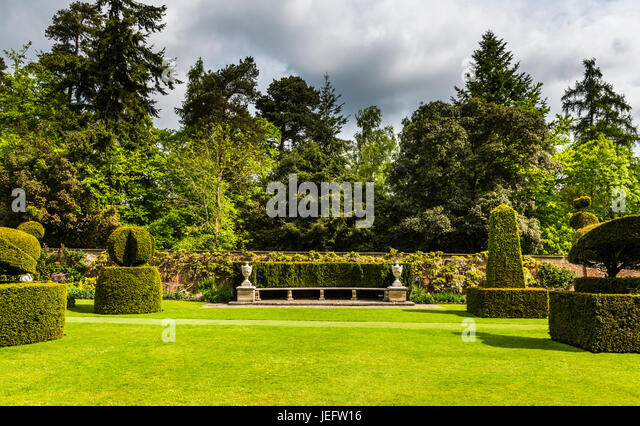 Stone seat and topiary in the gardens at Cliveden, Buckinghamshire, UK - Stock Image