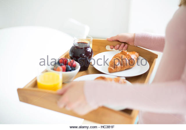 Young woman carrying food tray. - Stock Image