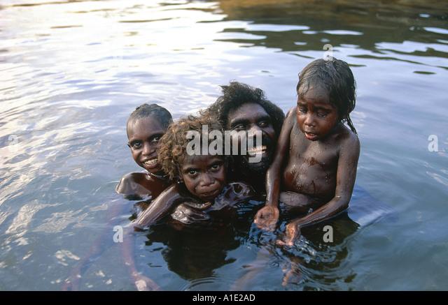 Aboriginal elder Billy Nalakandi with his children Rayhab Romeo and Susannah cool-off and play in Kubumi billabong - Stock-Bilder