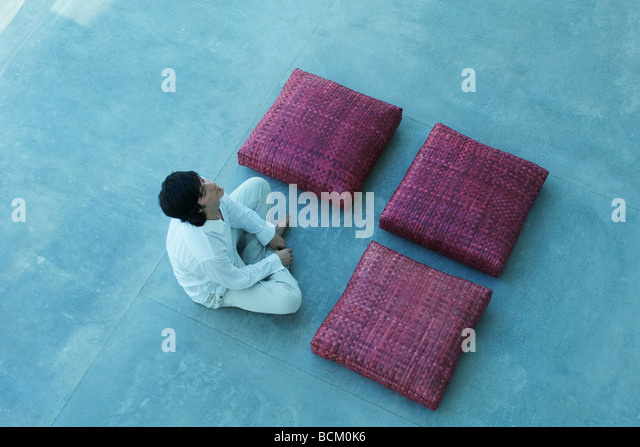 Three square cushions and man arranged in square shape, man crossing legs, closing eyes, high angle view - Stock-Bilder