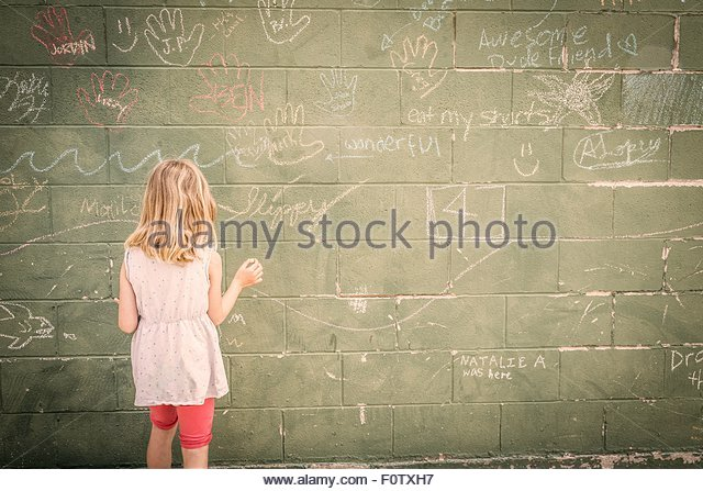 Girl in front of wall with chalk drawings, rear view - Stock Image