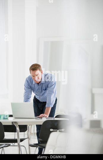 Business. A man standing over a desk, leaning down to use a laptop computer. - Stock-Bilder
