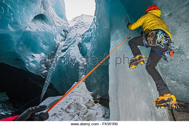 Ice climbers climbing up ice cave below the Gigjokull glacier, Thorsmork, Iceland - Stock-Bilder