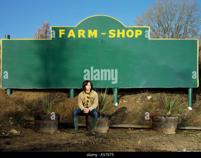 Young man outside a Farm Shop - Stock Image