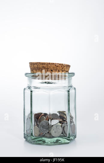 Jar half full of UK sterling coins. - Stock Image