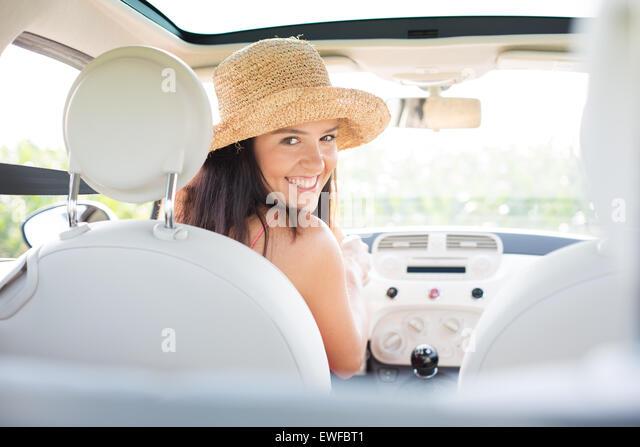 Portrait of beautiful woman driving car - Stock Image