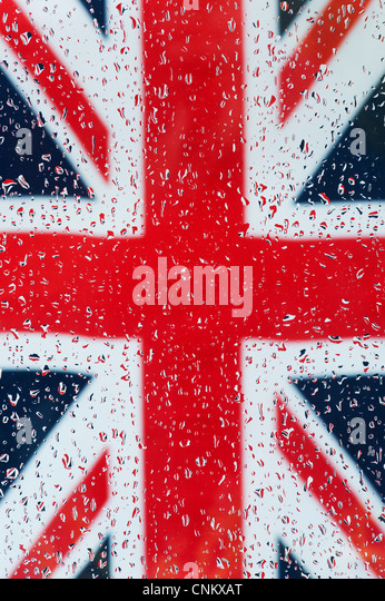 Raindrops on glass in front of a Union jack flag - Stock Image