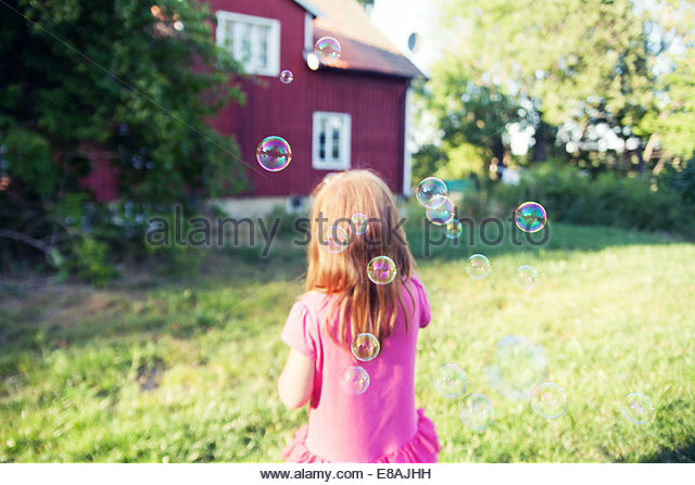 Rear view of girl blowing bubbles in garden - Stock Image