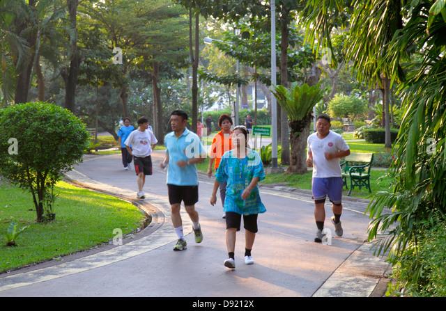 Bangkok Thailand Phra Nakhon Saranrom Park Asian man woman jogging running walking exercising path - Stock Image