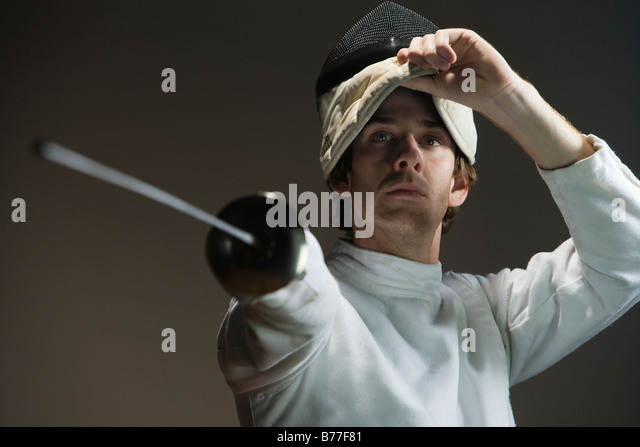 Man pointing fencing foil and lifting mask - Stock Image