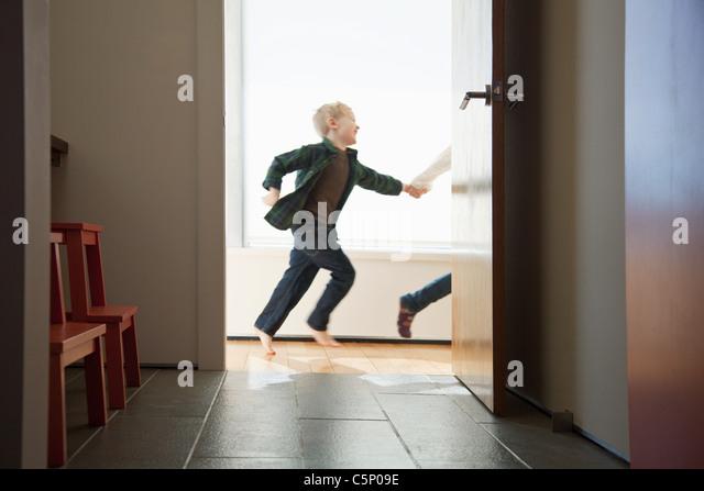 Two children running past doorway - Stock-Bilder