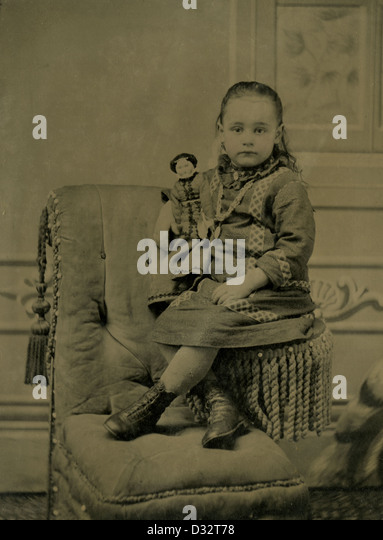 Circa 1870s tintype photograph, a little girl with her Victorian doll. - Stock Image