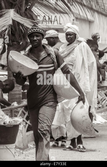 Mbour, Senegal - July, 2014: A man carries large bowls to sell on the street markets on July 9, 2014 in Mbour, Senegal. - Stock Image