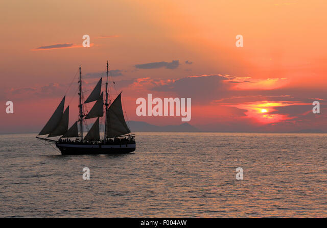 sailing ship at sunset, Greece, Cyclades, Santorin - Stock Image