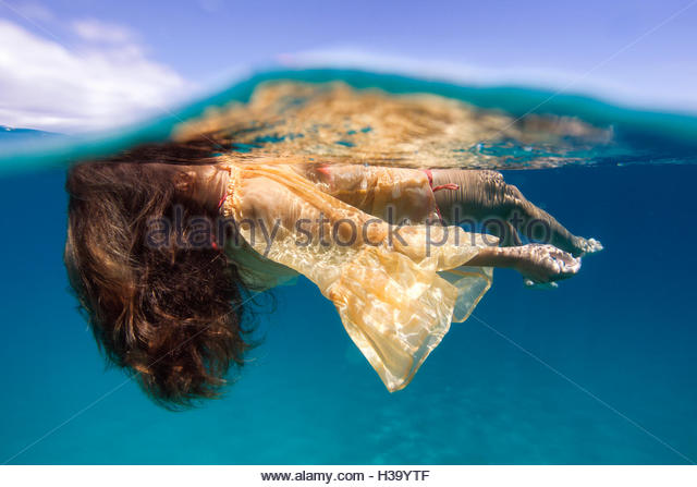 woman floating on her back in the opened ocean with a dress on - Stock Image
