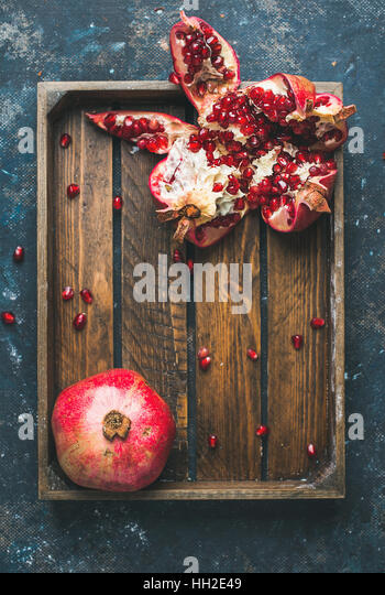 Fresh ripe pomegranates cut in pieces in wooden tray - Stock Image