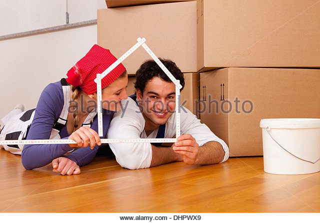 couple young moving in new home house frame ruler - Stock Image